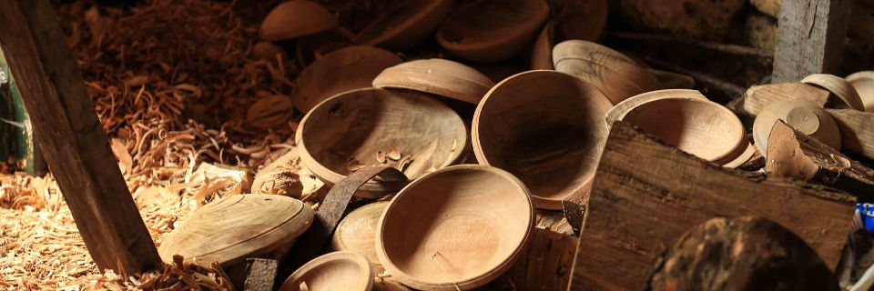 a pile of wooden bowls on the workshop floor