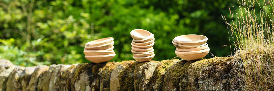 3 stacks of wooden bowls on a wall